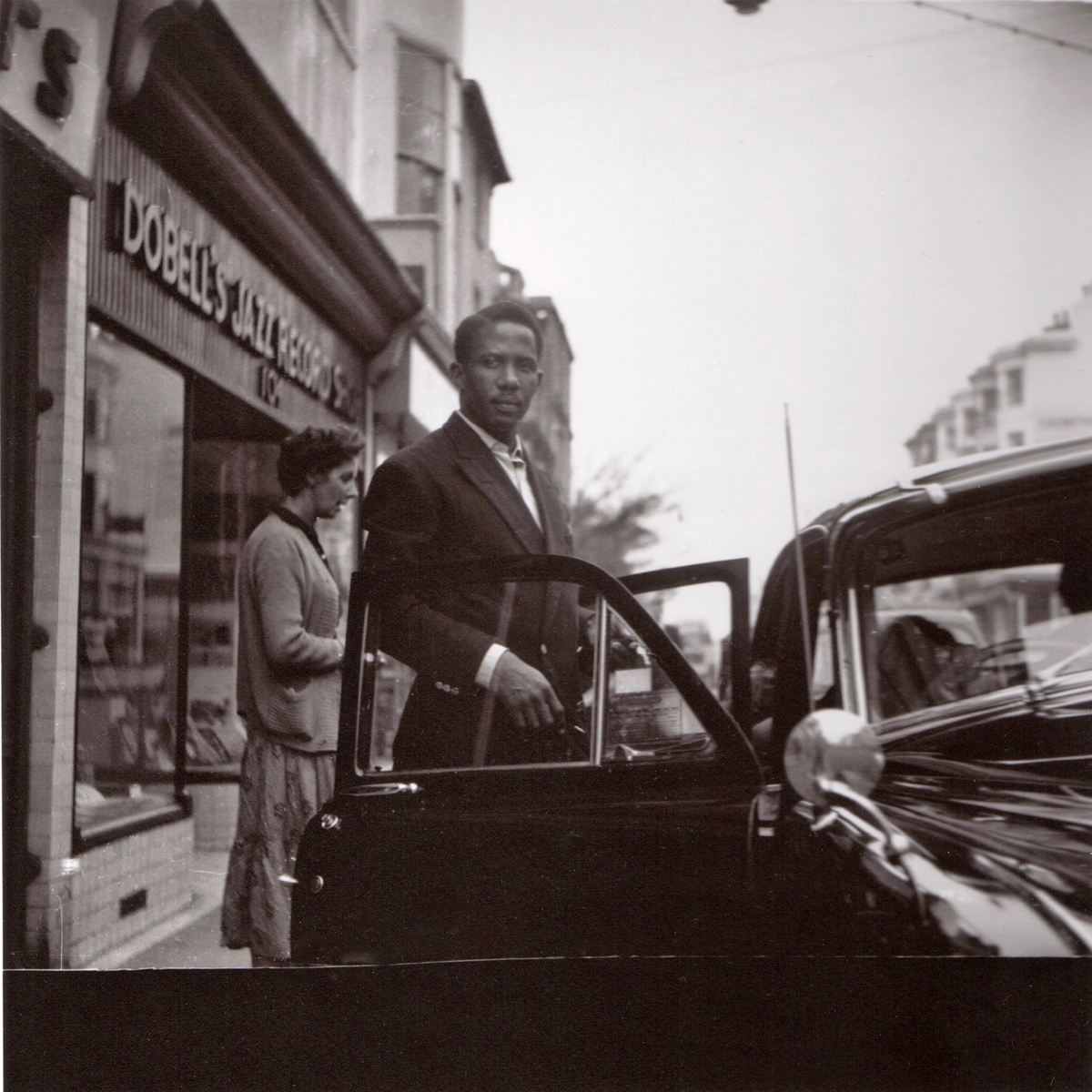Unknown man outside shop, possibly Pete Martin's wife Joyce behind him.