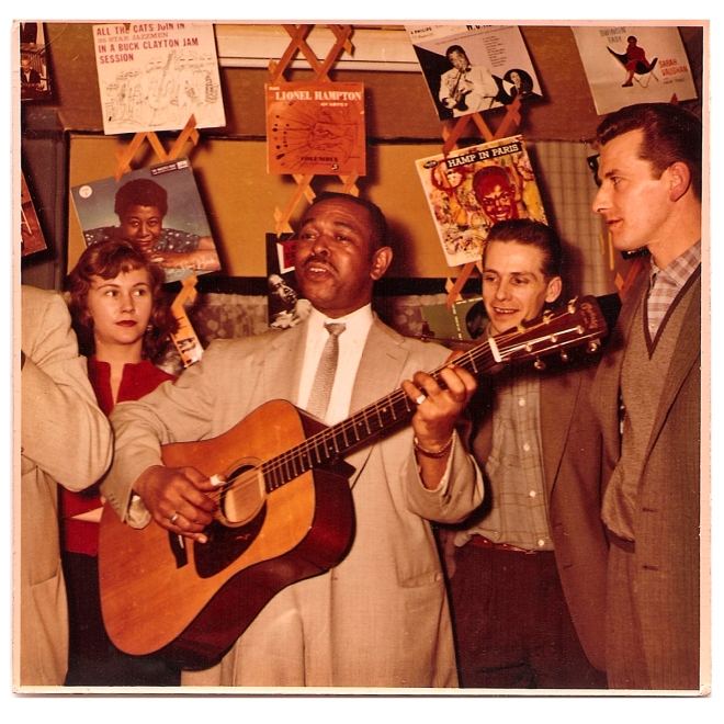 Ron & Mina Bowden and Bill look on as Brownie McGhee and Sonny Terry (cut off) play in the shop.